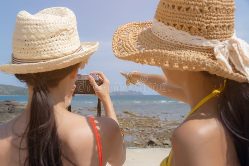 Mulheres bonitas do viajante ou amigo bonito que dizem seu amigo para tomar a foto bonita na praia bonita na temporada de verão imagem de stock royalty free