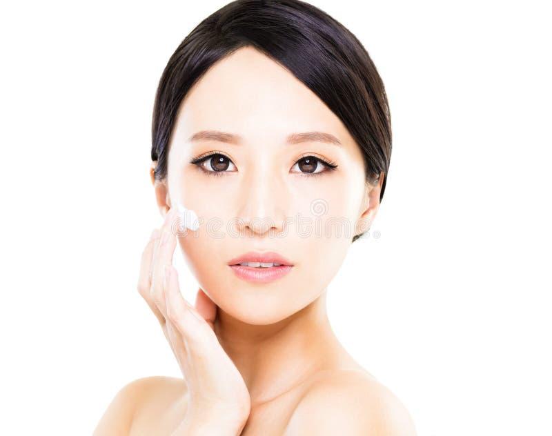Mulheres bonitas que aplicam o creme cosmético do creme hidratante na cara fotografia de stock