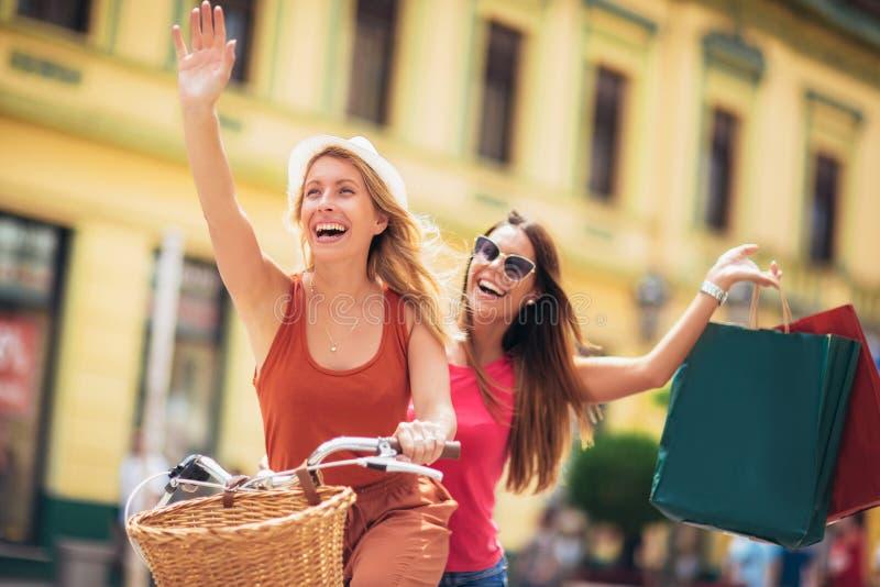 Mulheres bonitas que compram na bicicleta na cidade imagens de stock