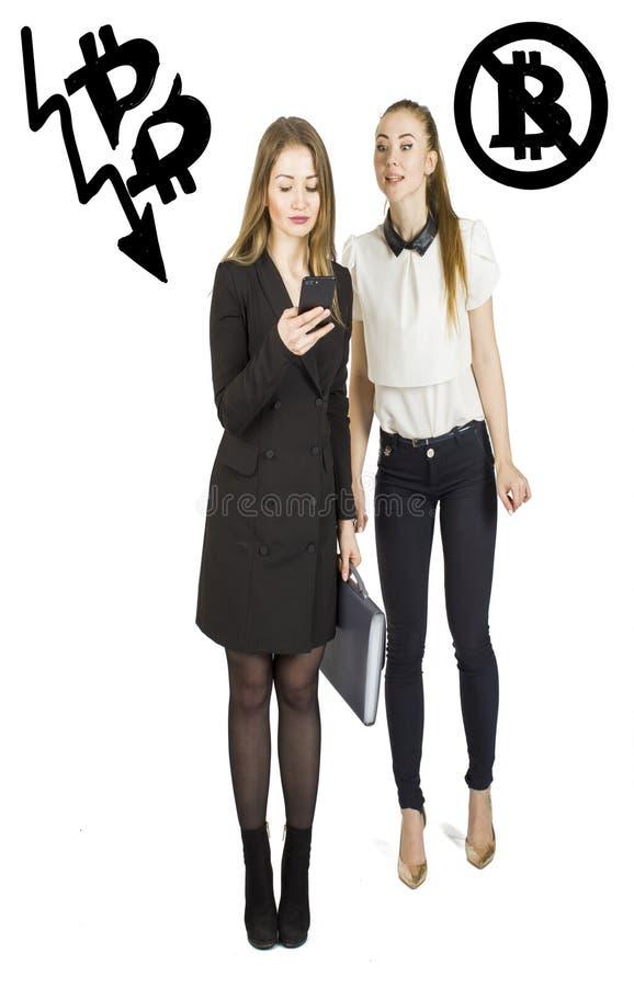 Mulheres bonitas que estão sobre o fundo branco com esboços e fala do bitcoin Conceito virtual do dinheiro Cryptocurrency fotografia de stock