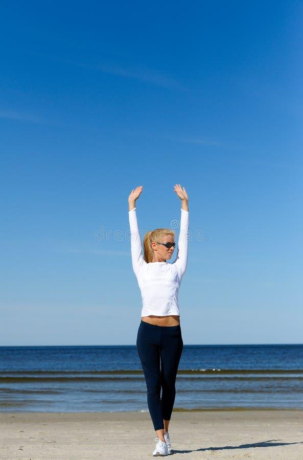 Mulheres bonitas que exercitam na praia foto de stock