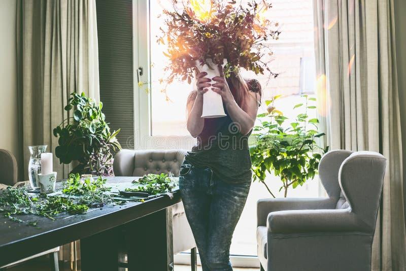 Mulheres bonitas que guardam o vaso com o ramalhete do verão de flores selvagens em suas mãos na sala de visitas com tabela e pol fotos de stock