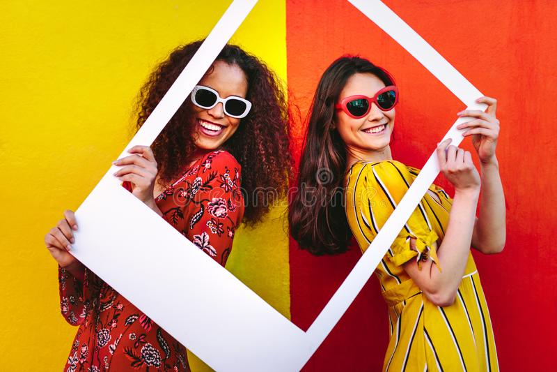 Mulheres bonitas que guardam um quadro vazio da foto foto de stock royalty free