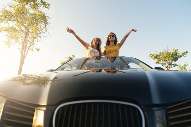 Mulheres bonitas que têm o divertimento no carro do te fotografia de stock