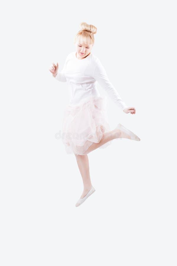 Mulheres caucasianos novas na saia branca da camisa e do tutu que salta altamente com alegria no fundo branco isolado imagens de stock