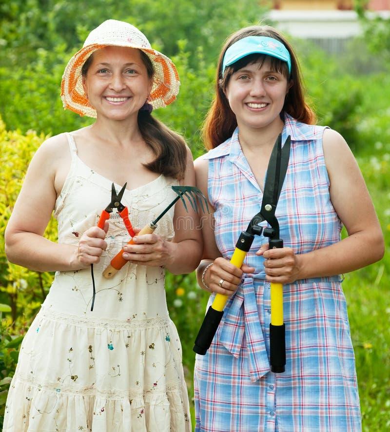Mulheres com as ferramentas de jardim na jarda fotografia de stock royalty free
