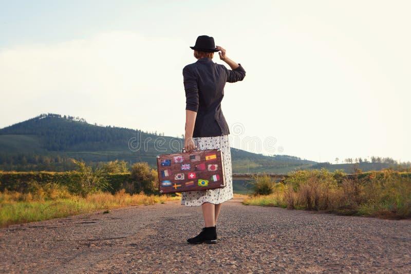 Mulheres com a mala de viagem do curso do vintage na estrada fotografia de stock royalty free