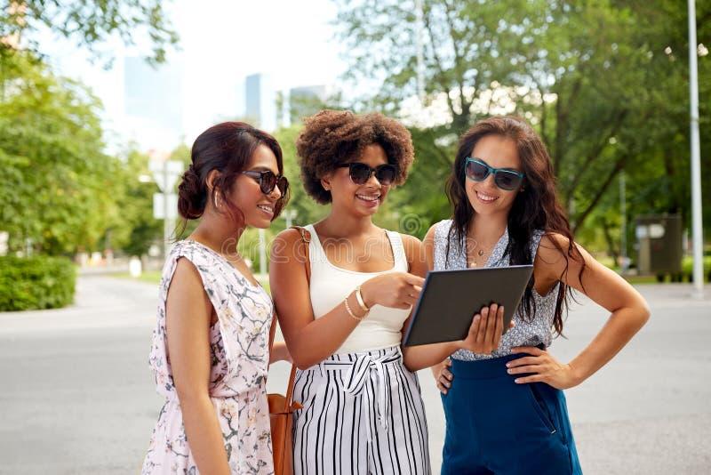 Mulheres com o PC da tabuleta na rua no verão foto de stock