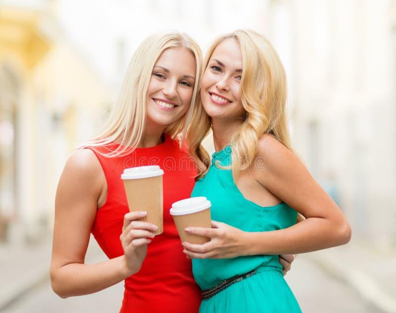 Mulheres com os copos de café afastados na cidade foto de stock royalty free