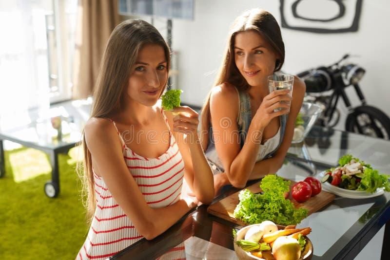 Mulheres comendo saudáveis que cozinham a salada na cozinha Alimento da dieta da aptidão imagens de stock