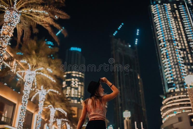 Mulheres consideráveis na roupa elegante do chapéu, homem brutal, equipamento à moda, caminhada abaixo da rua luz e palmas fresca imagem de stock