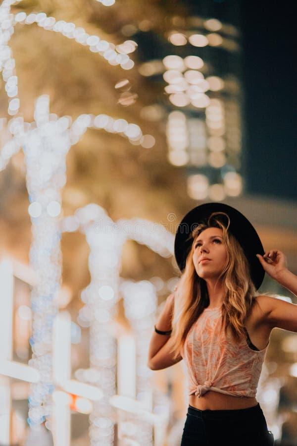 Mulheres consideráveis na roupa elegante do chapéu, homem brutal, equipamento à moda, caminhada abaixo da rua luz e palmas fresca imagens de stock