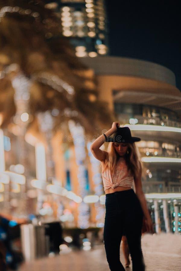 Mulheres consideráveis na roupa elegante do chapéu, homem brutal, equipamento à moda, caminhada abaixo da rua luz e palmas fresca imagem de stock royalty free
