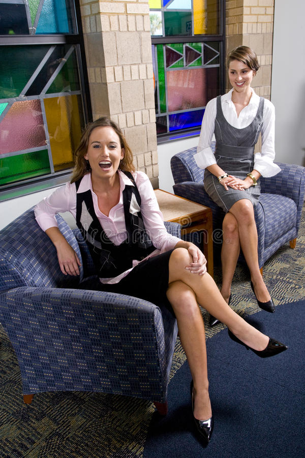 Mulheres consideravelmente novas que sentam-se na cadeira da sala de espera foto de stock