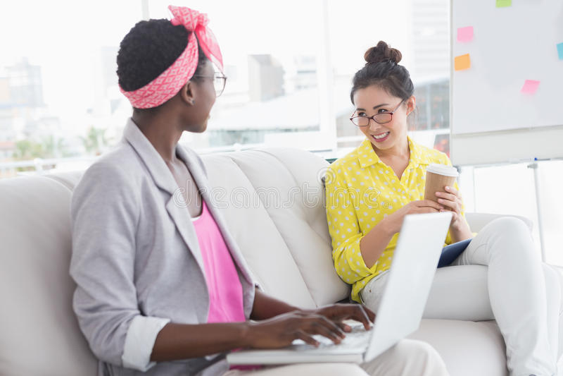 Mulheres criativas novas que conversam no sofá fotografia de stock