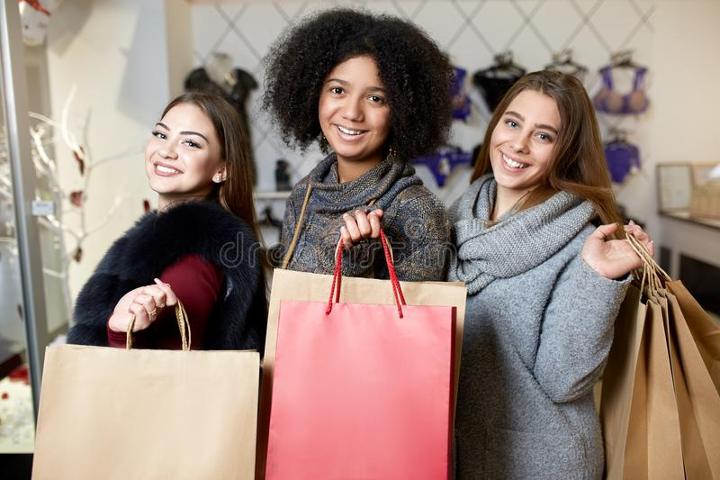 Mulheres da afiliação étnica diversa com os sacos de compras que levantam na loja da roupa interior Retrato de três meninas consi fotografia de stock royalty free