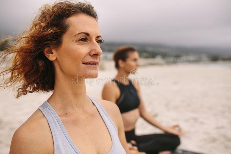 Mulheres da aptidão que fazem a ioga que senta-se na praia imagem de stock royalty free