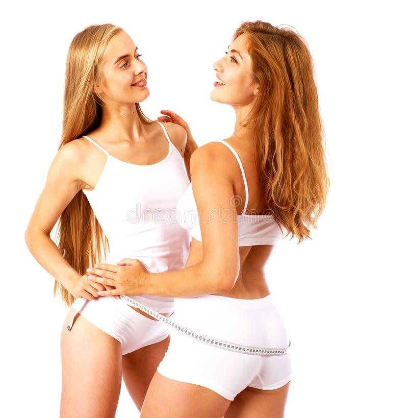 Mulheres da aptid?o Duas amigas bonitas novas no sportswear branco imagem de stock