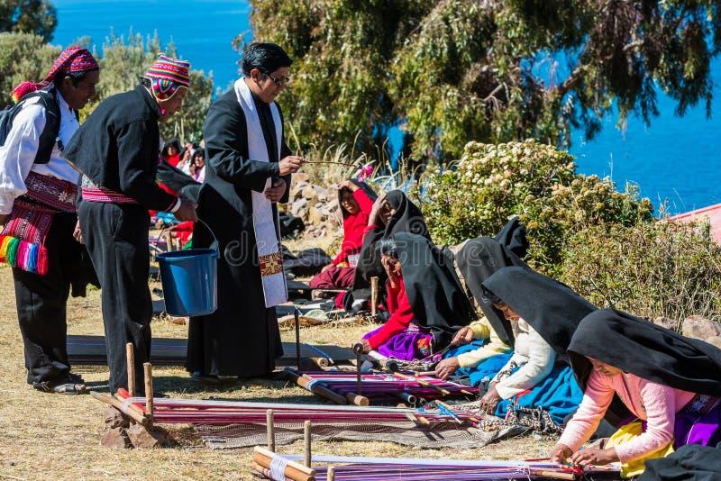 Mulheres da bênção do padre que tecem no Peru de Puno imagens de stock
