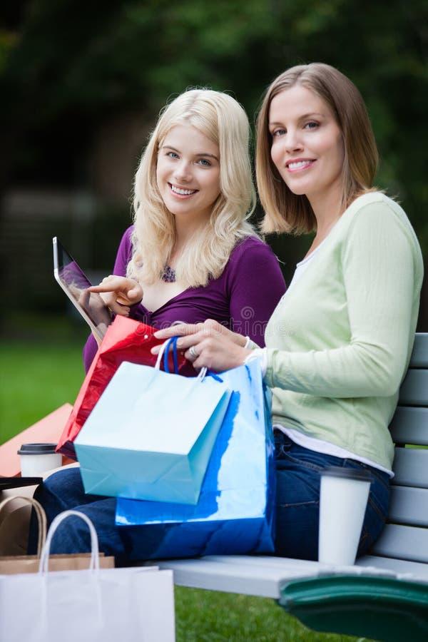 Mulheres da compra que usam a tabuleta de Digitas imagens de stock royalty free