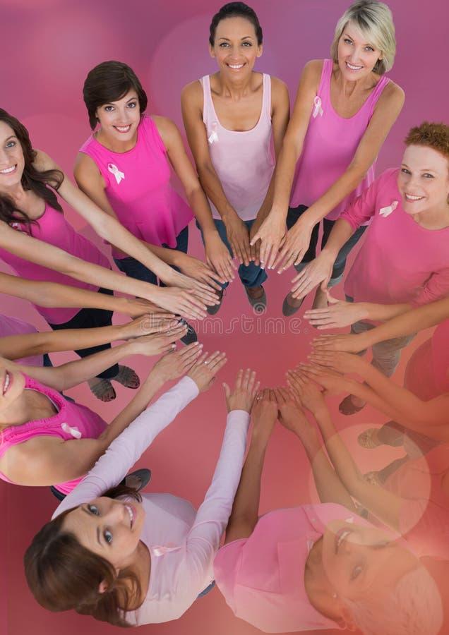 Mulheres da conscientização do câncer da mama que unem as mãos fotografia de stock