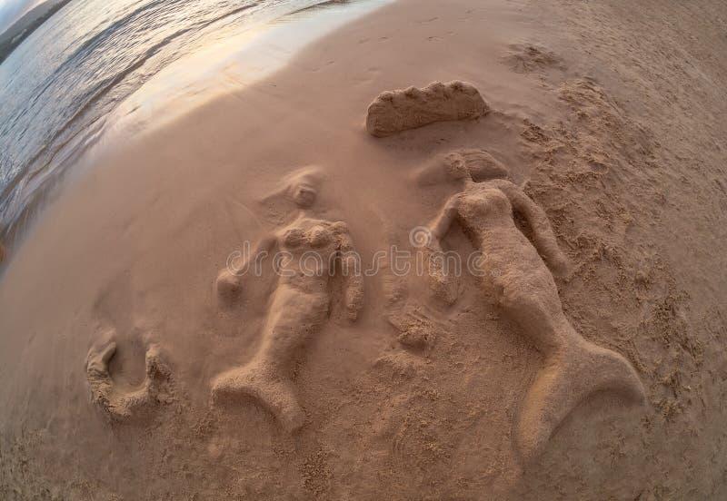 Mulheres da sereia que tiram na areia fotografia de stock
