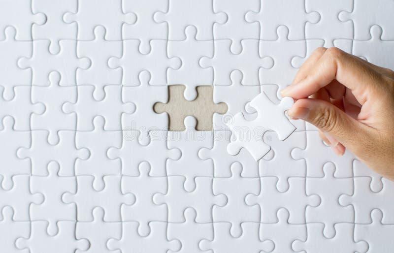 Mulheres das m?os que p?em a cor branca do enigma de serra de vaiv?m, grade das partes do enigma, trabalhos de equipe bem sucedid foto de stock