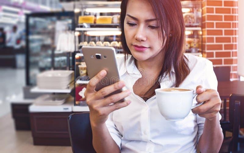 Mulheres de Ásia que bebem o café e olham seu telefone celular no sa imagem de stock