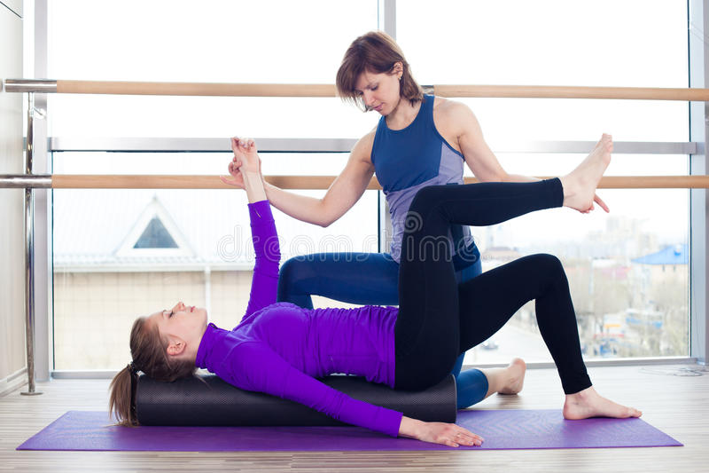 Mulheres de ajuda do instrutor pessoal de Pilates da ginástica aeróbica imagens de stock