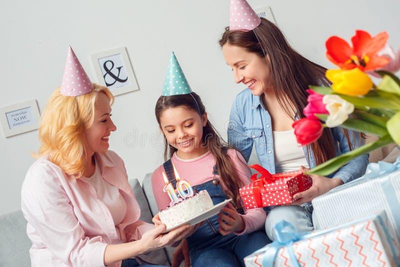 Mulheres de assento do aniversário da mãe e da filha da avó junto em casa que dão o sorriso do bolo e do presente da menina feliz foto de stock