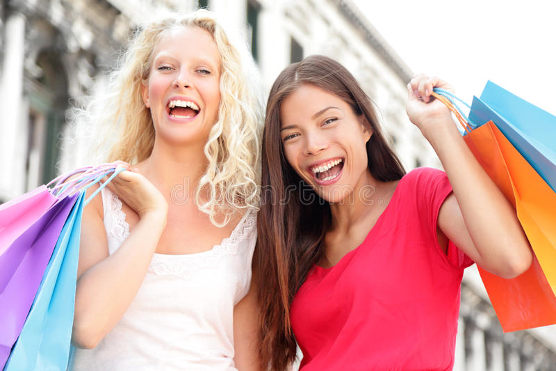 Mulheres de compra dos amigos entusiasmado e felizes fotografia de stock royalty free
