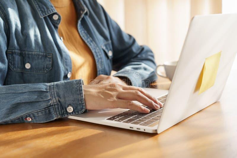 Mulheres de funcionamento da mão do close-up que usam o teclado no portátil no hom, luz solar morna da manhã fotografia de stock