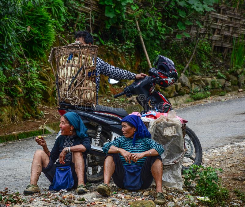Mulheres de Hmong que sentam-se na estrada rural imagens de stock