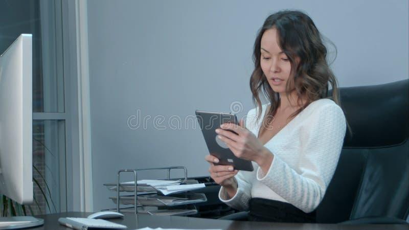 Mulheres de negócio asiáticas que trabalham o laptop e a tabuleta digital no escritório foto de stock