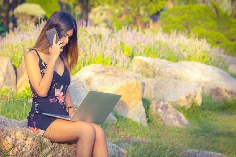 Mulheres de negócio atrativas que usam o telefone e o portátil quando se sente em uma pedra no parque durante o dia foto de stock royalty free