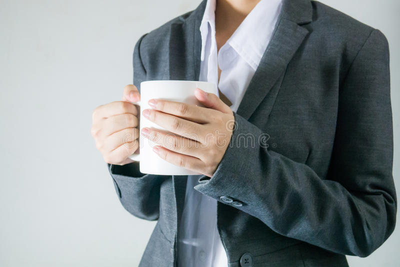 Mulheres de negócio pretas do terno que guardam uma xícara de café no tempo da ruptura imagens de stock royalty free
