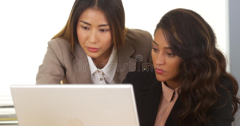 Mulheres de negócios da raça misturada que trabalham junto no portátil imagem de stock
