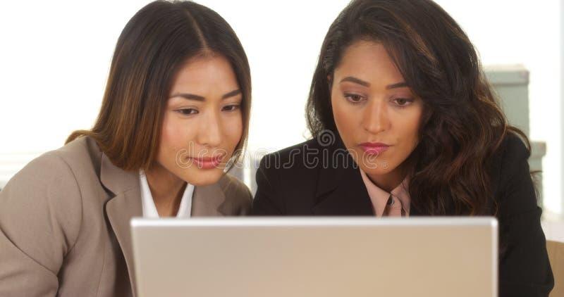 Mulheres de negócios da raça misturada que trabalham no portátil fotos de stock royalty free