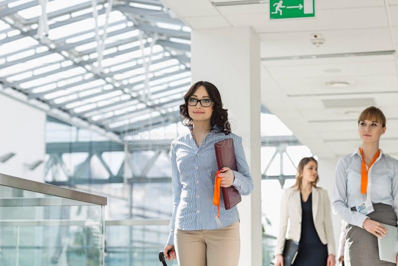 Mulheres de negócios de sorriso com bagagem e arquivo que andam no aeroporto foto de stock royalty free