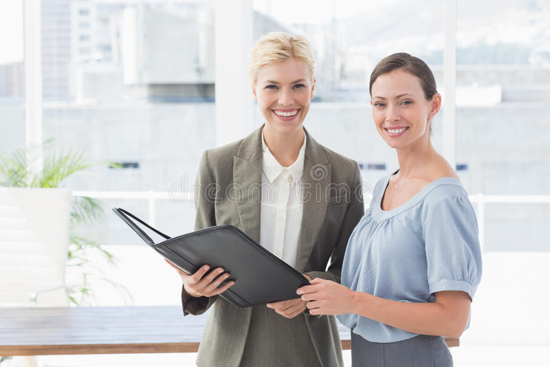 Mulheres de negócios de sorriso que olham a câmera e que trabalham junto fotografia de stock