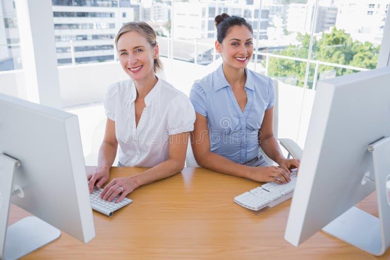 Mulheres de negócios de sorriso que trabalham de lado a lado foto de stock