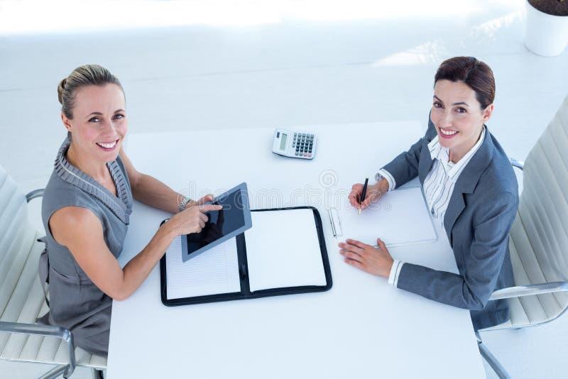 Mulheres de negócios de sorriso que trabalham junto fotografia de stock royalty free