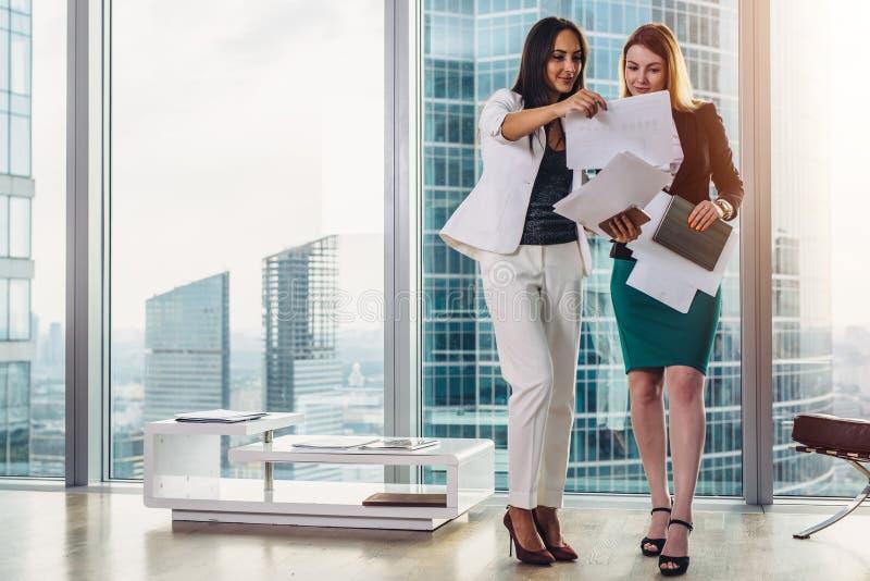 Mulheres de negócios fêmeas que vestem o equipamento formal que discute os originais que estão no corredor do escritório fotografia de stock royalty free