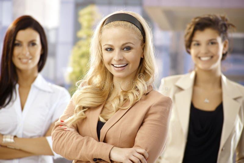 Mulheres de negócios felizes que estão os braços cruzados foto de stock royalty free