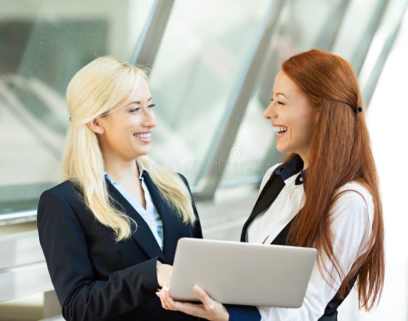 Mulheres de negócios felizes que sorriem, discutindo um negócio, guardando o computador foto de stock royalty free