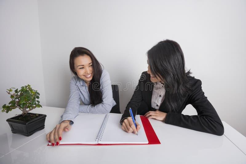 Mulheres de negócios felizes que trabalham na mesa no escritório fotografia de stock
