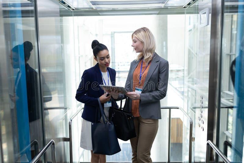 mulheres de negócios Multi-étnicas que discutem sobre a tabuleta digital no elevador do escritório imagem de stock