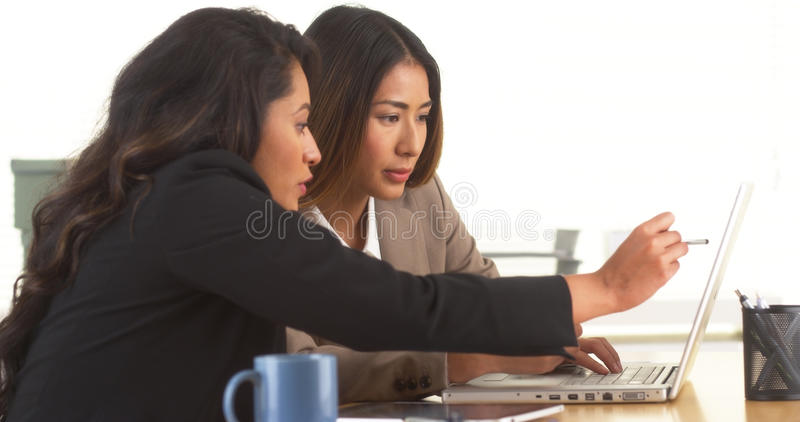 mulheres de negócios Multi-étnicas que fazem a pesquisa na mesa fotos de stock royalty free
