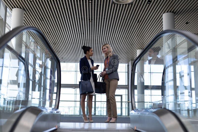 mulheres de negócios Multi-étnicas que interagem um com o otro no escritório moderno imagens de stock royalty free