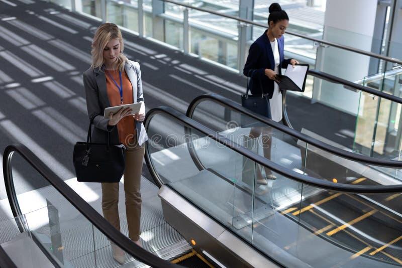 mulheres de negócios Multi-étnicas que usam a escada rolante no escritório moderno fotos de stock
